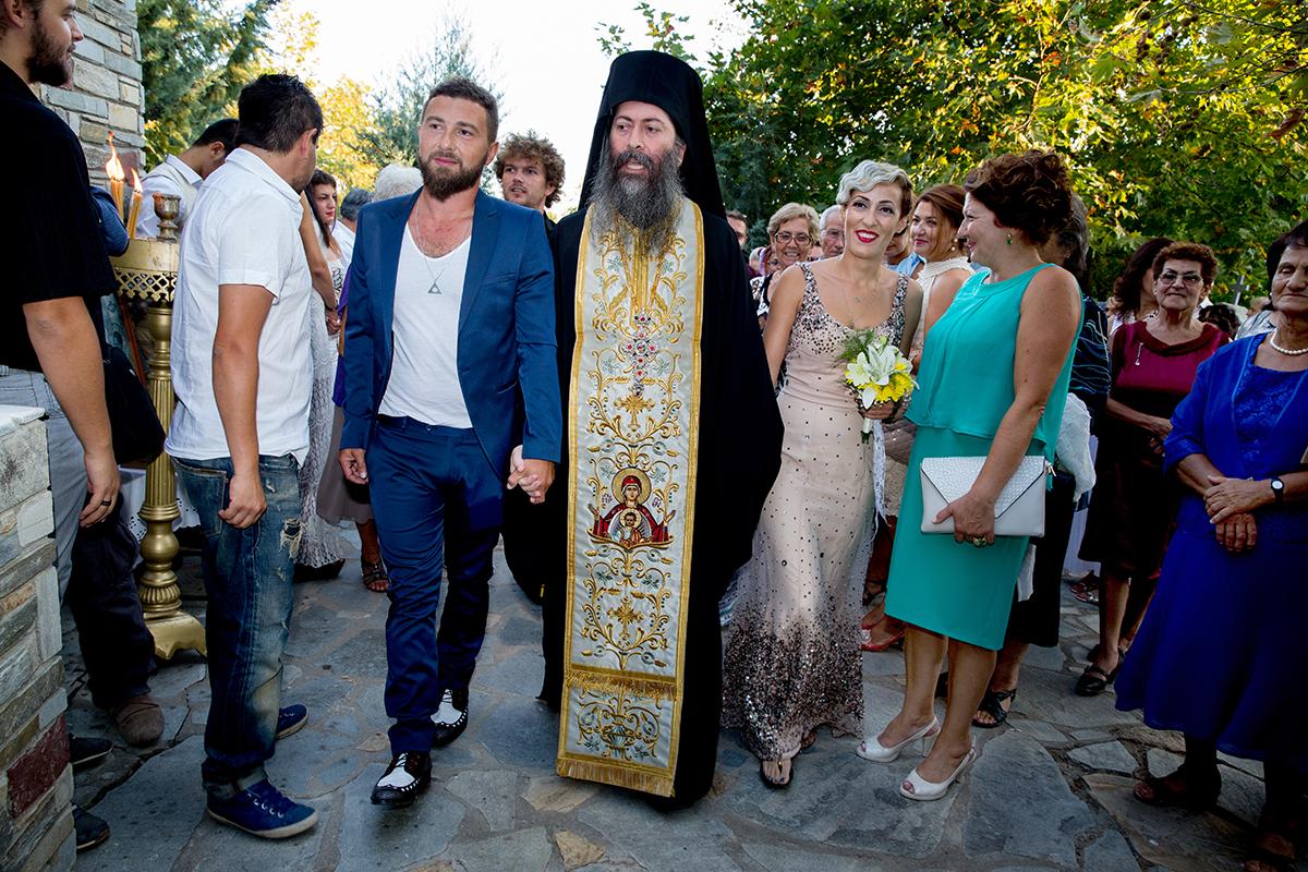 η φωτογράφηση γάμου του Αποστόλη και της Νένας.ο παπάς έχει πιάσει τα χέρια των νεόνυμφων και τους οδηγεί στην εκκλησία