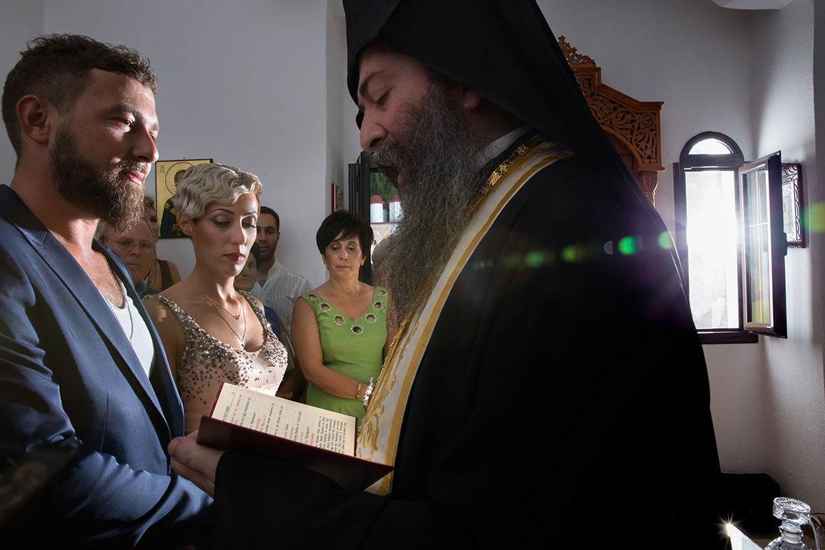 η φωτογράφηση γάμου του Αποστόλη και της Νένας.ο παπάς και το ζευγάρι απέναντι.φως μπαίνει από το παράθυρο της εκκλησίας.φωτογραφία γάμου
