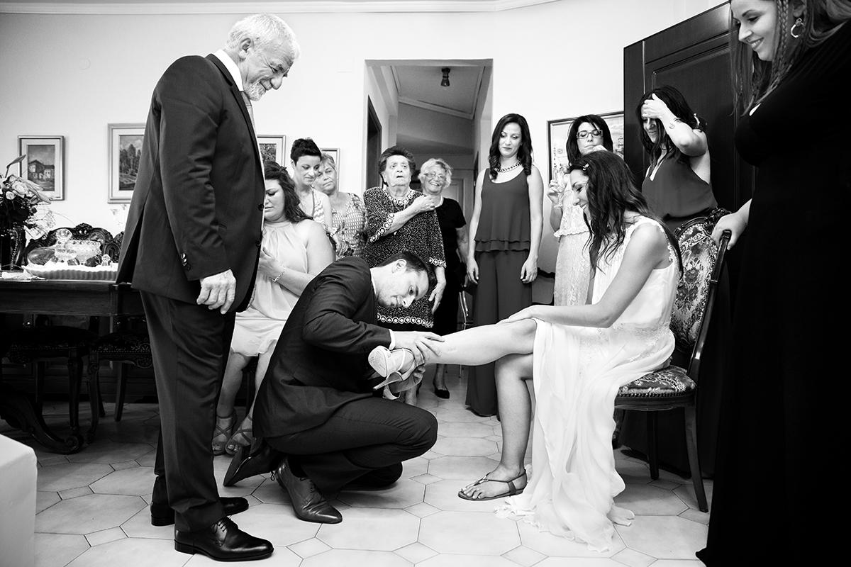 ασπρόμαυρη φωτογραφία γάμου. ο αδελφός τοποθετεί το παπούτσι στο πόδι της νύφης.φωτογραφία γάμου.Ο γάμος της Ροζμαρί και του Μάκη