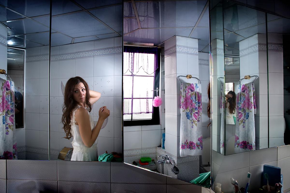 η νύφη κοιτάει στον καθρέπτη της τουαλέτας.από φωτογράφιση γάμου στην πόλη της θεσσαλονίκης.φωτογραφία γάμου.Ο γάμος της Ροζμαρί και του Μάκη