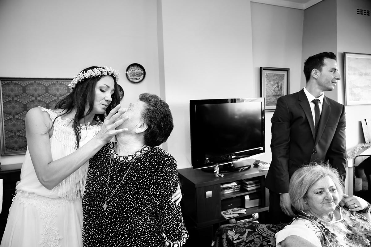 φωτογραφία γάμου.Ο γάμος της Ροζμαρί και του Μάκη.η νύφη πάει να πιάσει το πρόσωπο της γιαγιά της προς ένδειξη αγάπης.μια ακόμα ασπρόμαυρη φωτογραφία γάμου από τη θεσσαλονίκη με αγάπη.