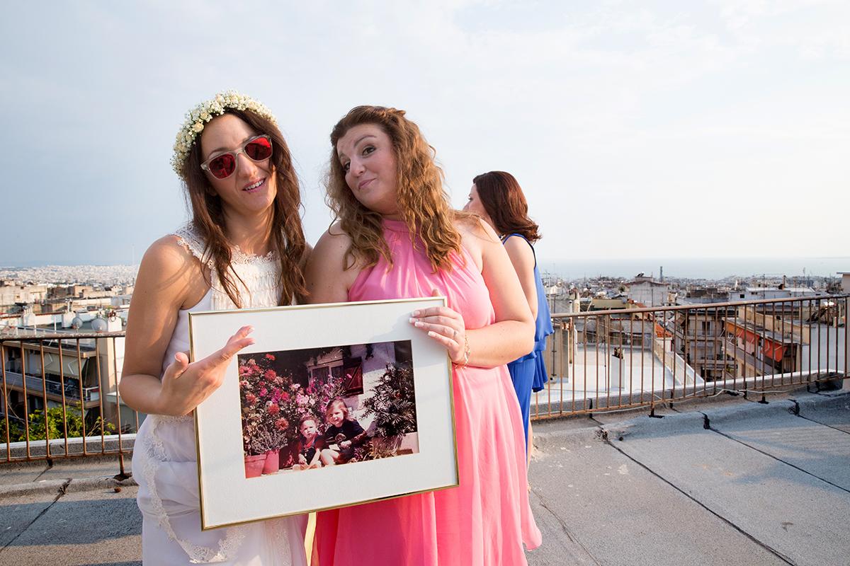 φωτογραφία γάμου.Ο γάμος της Ροζμαρί και του Μάκη.η νύφη και η αδελφή της κρατάνε στα χέρια φωτογραφία τους.από φωτογράφιση γάμου σε ταράτσα της θεσσαλονίκης.