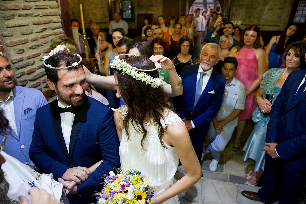 φωτογραφία γάμου.Ο γάμος της Ροζμαρί και του Μάκη.ο γαμπρός κοιτάει τη νύφη και χαμογελάει.λήψη από ψηλά ,η κουμπαρα τους αλλάζει τα στέφανα.
