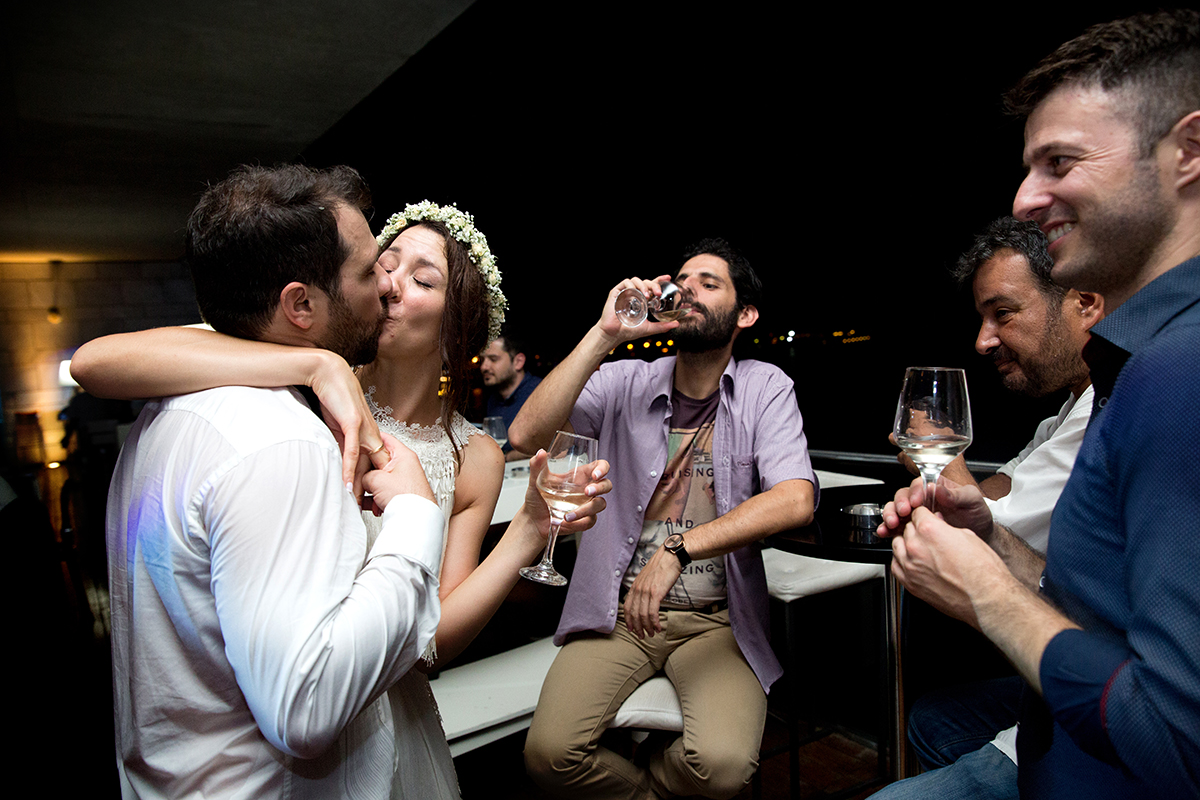 φωτογραφία γάμου.Ο γάμος της Ροζμαρί και του Μάκη.το ζευγάρι φιλιέται και ο φίλος τους πίσω από αυτούς, πίνει το κρασί του.φωτογραφία γάμου από το μέγαρο μουσικής θεσσαλονίκης.