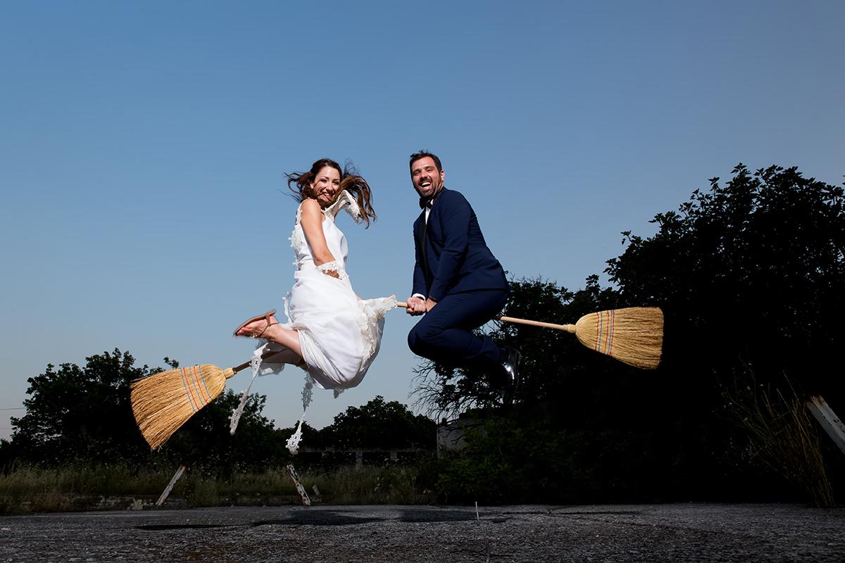 φωτογραφία γάμου στο στρατόπεδο κόδρα.το ζευγάρι κρατάει σκούπες ανάμεσα στα πόδια τους και πηδάει .φωτογράφιση γάμου στη πόλη της θεσσαλονίκης