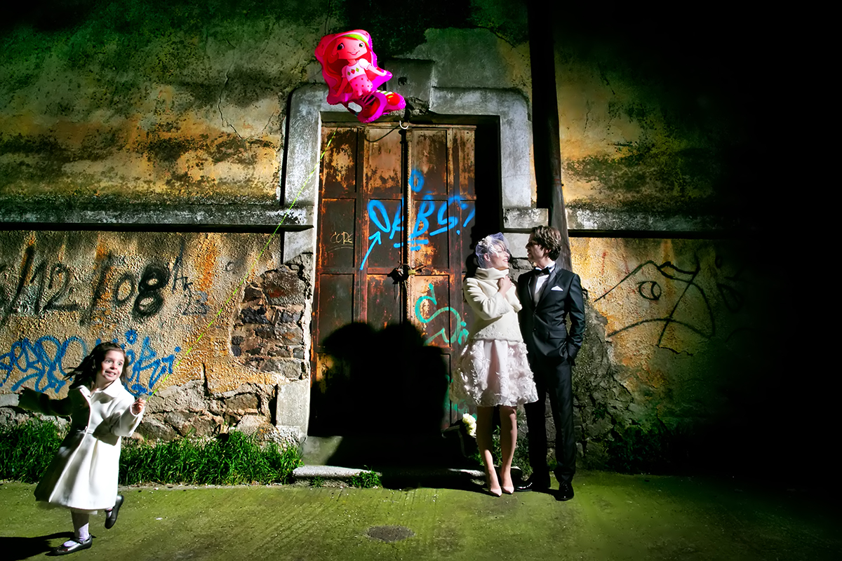 φωτογράφηση πολιτικού γάμου ,φωτογράφος γάμου από θεσσαλονίκη ,φωτογράφιση γάμου μέσα σε καπναποθήκη ,το ζεύγος χαμογελά ,κοριτσάκι με κόκκινο μπαλόνι τρέχει