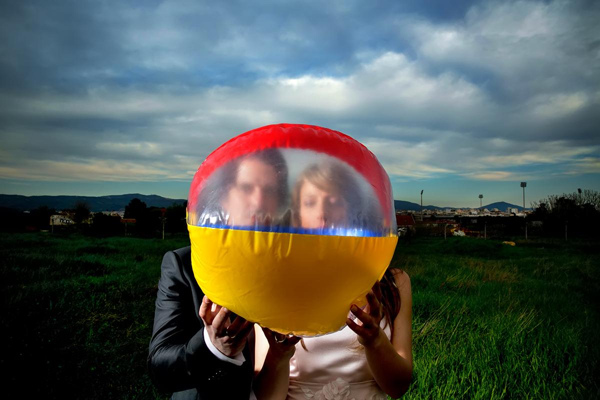 φωτογράφηση πολιτικού γάμου ,το ζευγάρι πίσω από μια μπάλα θαλάσσης.